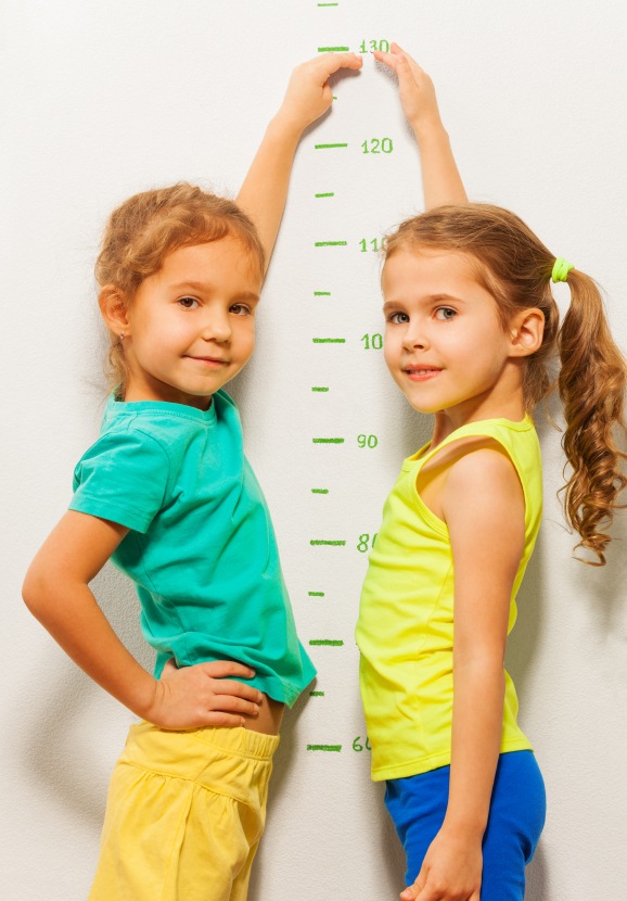 Two girls show height on the scale pretending to grow faster looking at camera and smiling