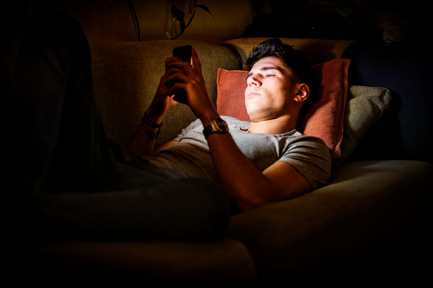 Attractive Young Man Lying on Sofa at Night and Illuminated by Light from Screen of Cell Phone at Home in Living Room