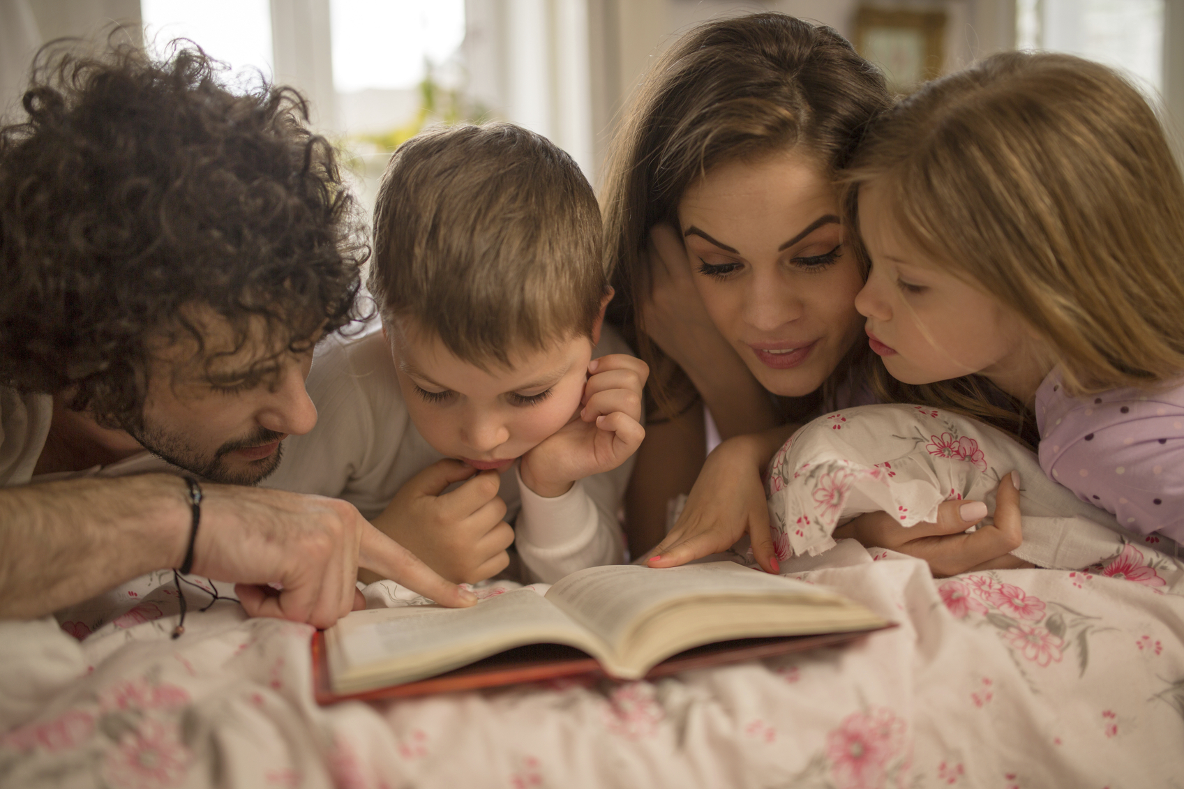 Young parents reading book together with their children in bedroom.