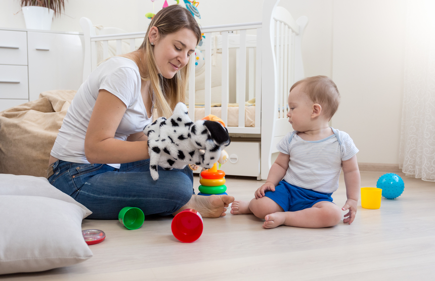 Beautiful smiling mother wearing dog puppet on hand and playing with her baby boy