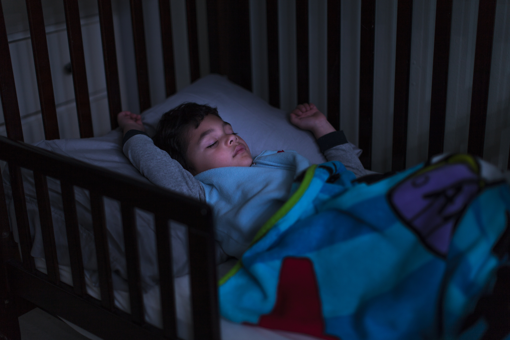 Stock photo of a young handsome boy sleeping in a bed with light on his face