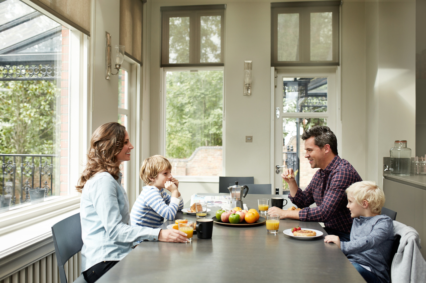 Shot of a smiling family of four eating breakfast together in their kitchen