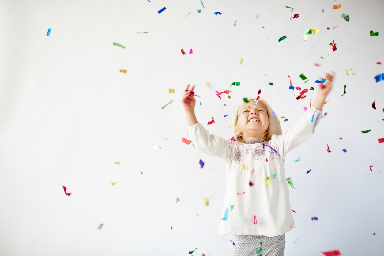 Ecstatic little girl catching falling confetti