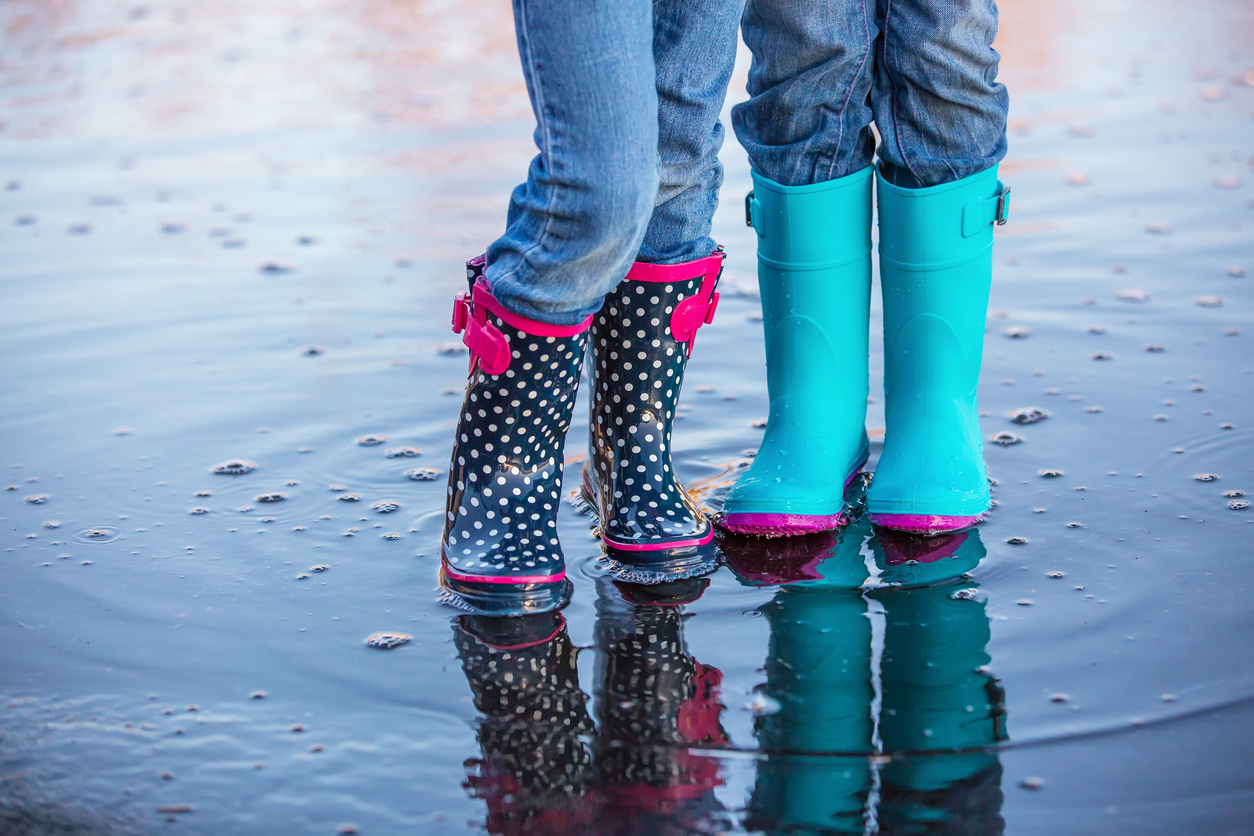 Waist down view of two children wearing rubber boots while standing side by side in a springtime water puddle. Both girls are wearing light blue denim jeans. The girl on the left has navy blue with white polka dots and pink trim on her boots. The girl on the right has light blue boots with pink bottoms.